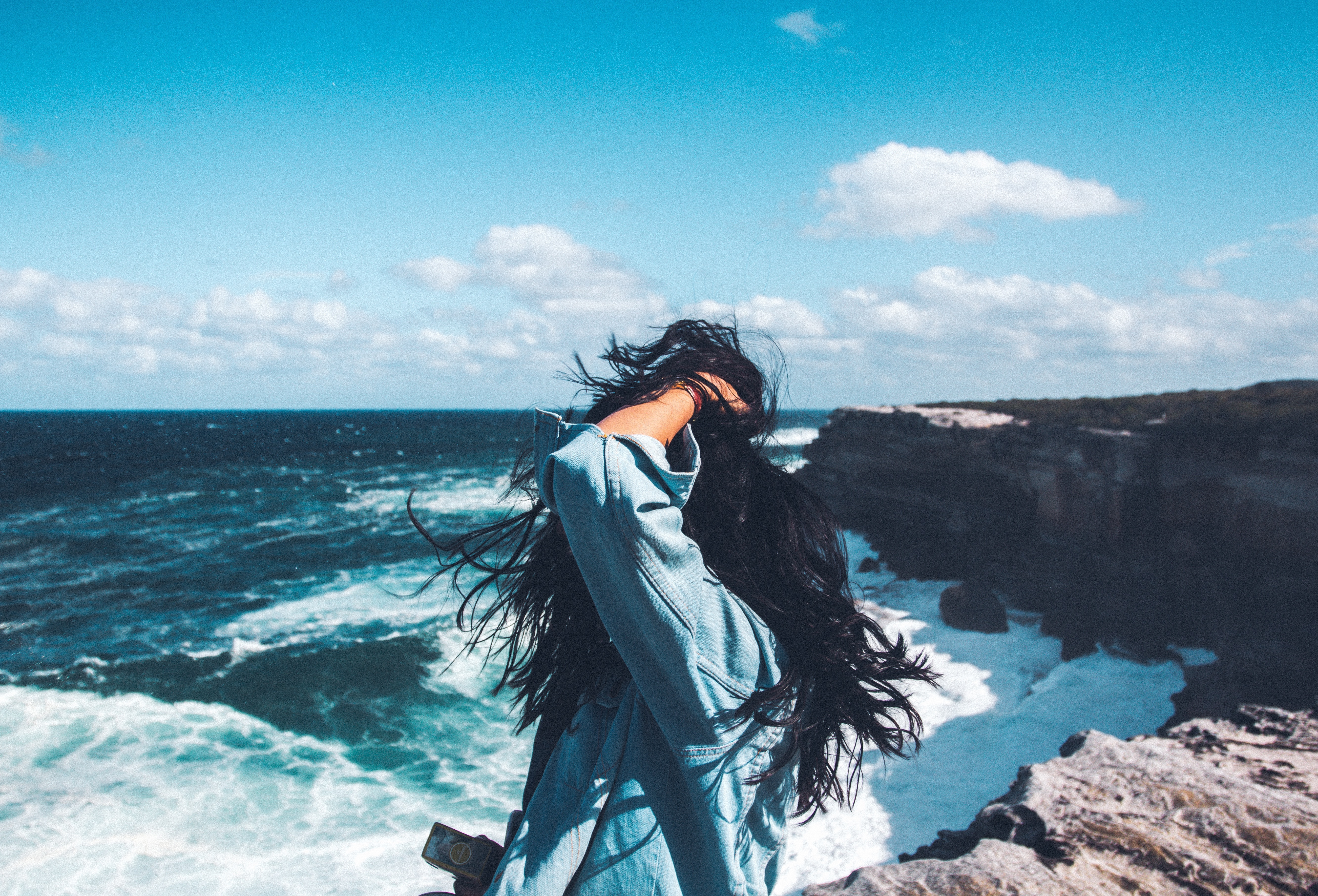 irl with hair all around her face standing by the ocean