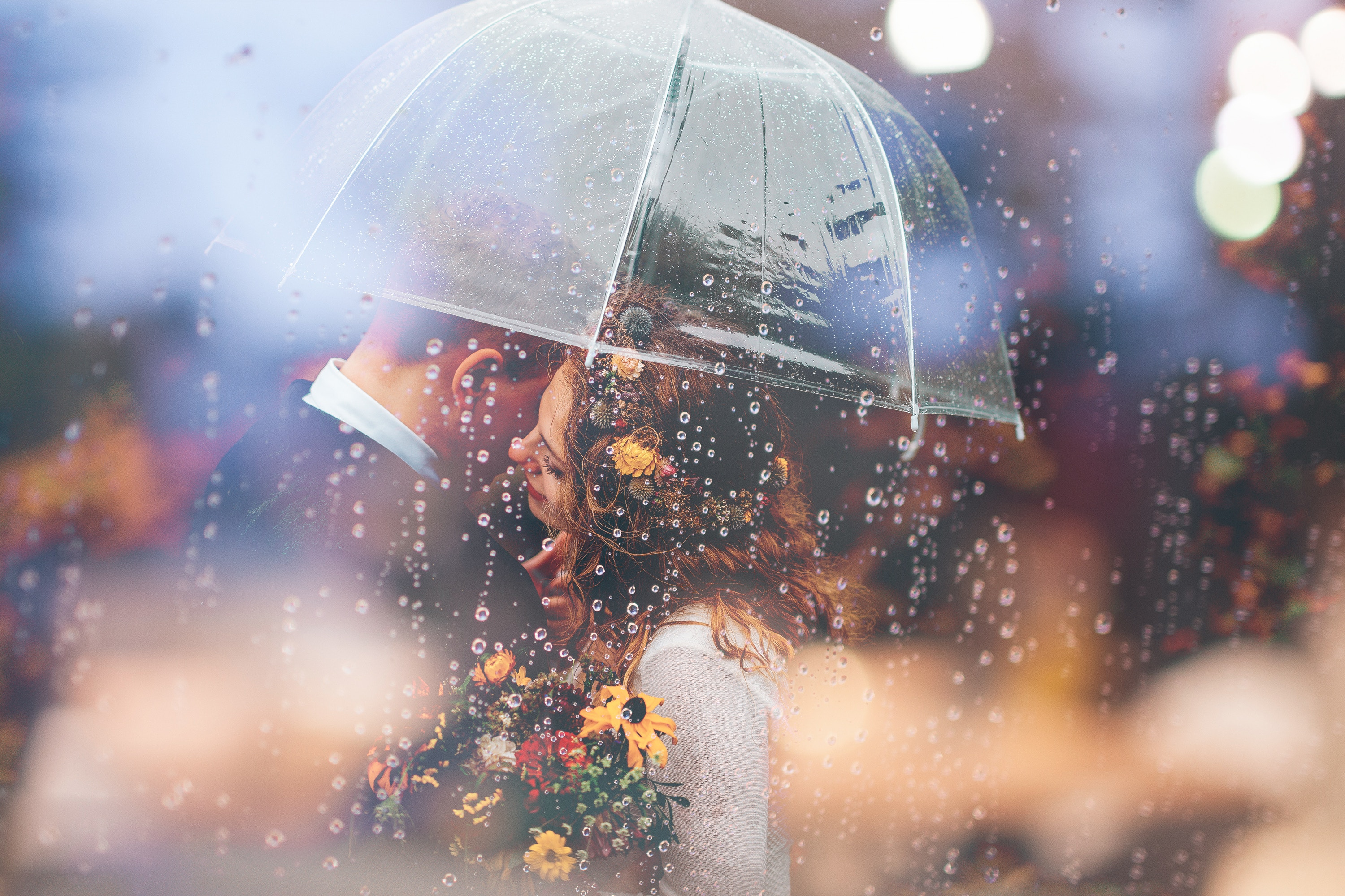 couple about to kiss in the rain under an umbrella