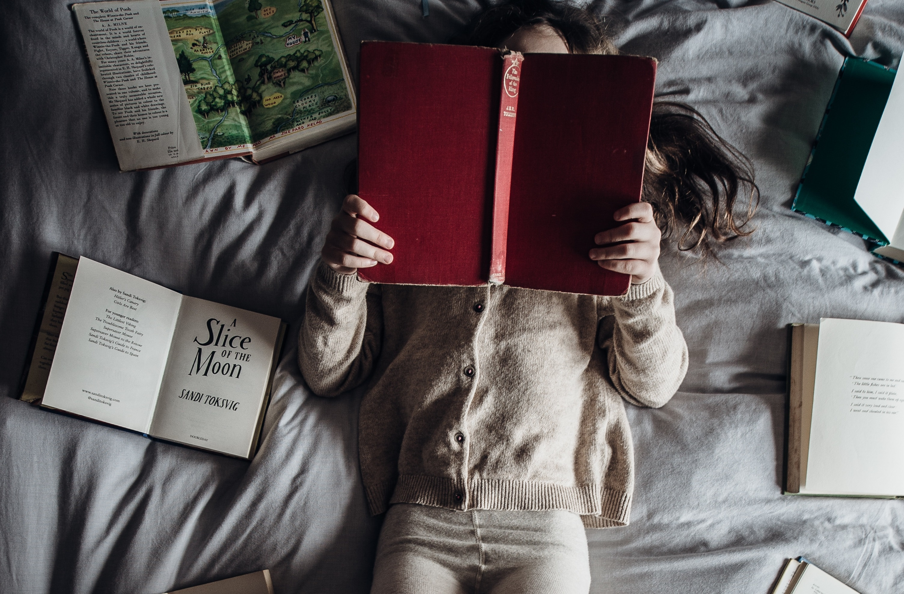 girl holding books on bed