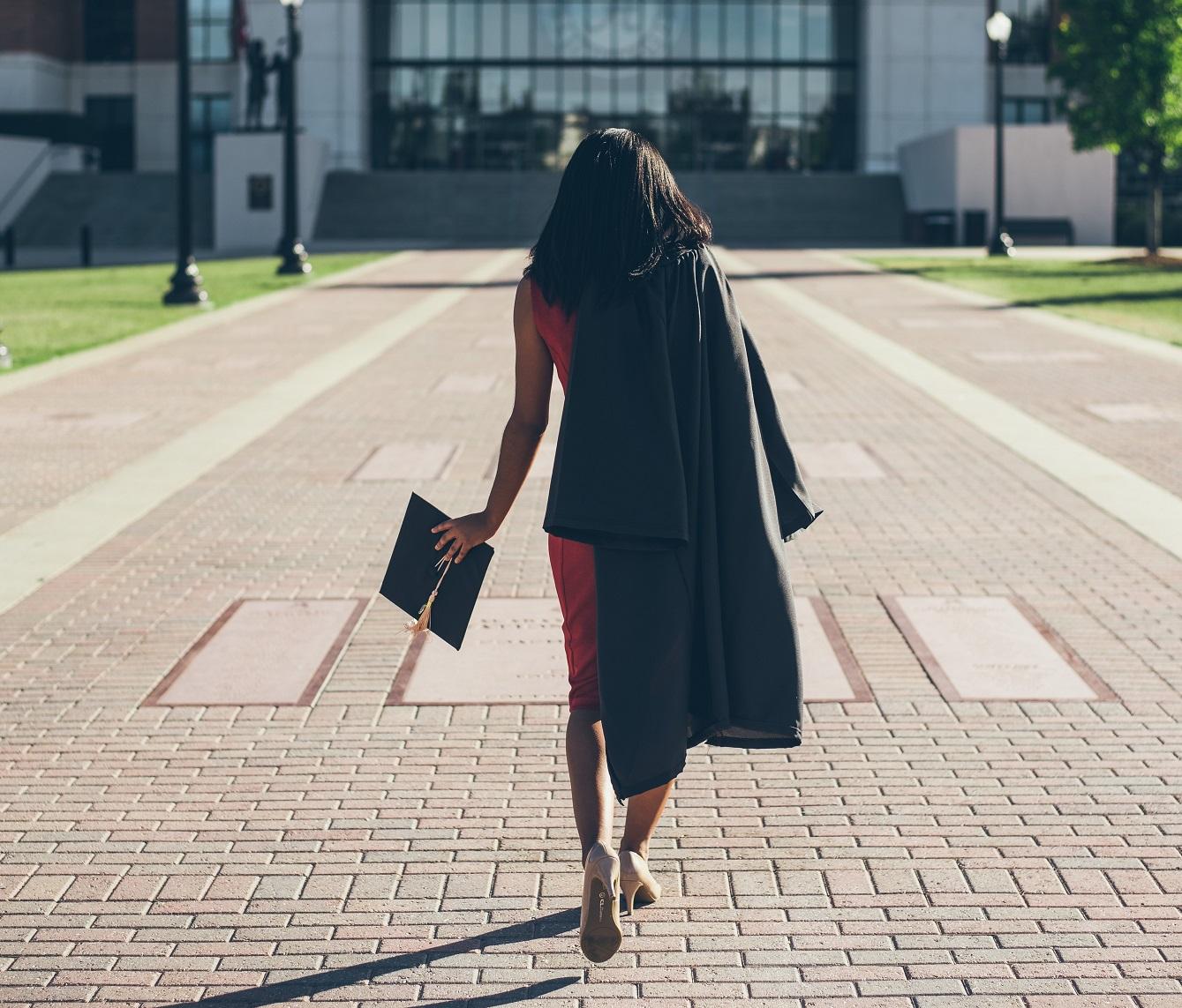 girl in graduation attire walking towards school