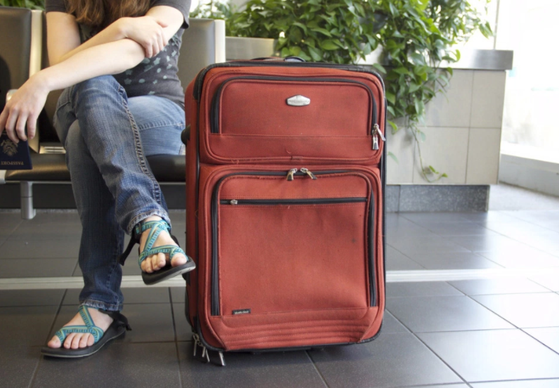 girl with red suitcase near her feet