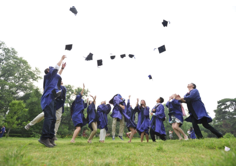 people throwing caps after graduating