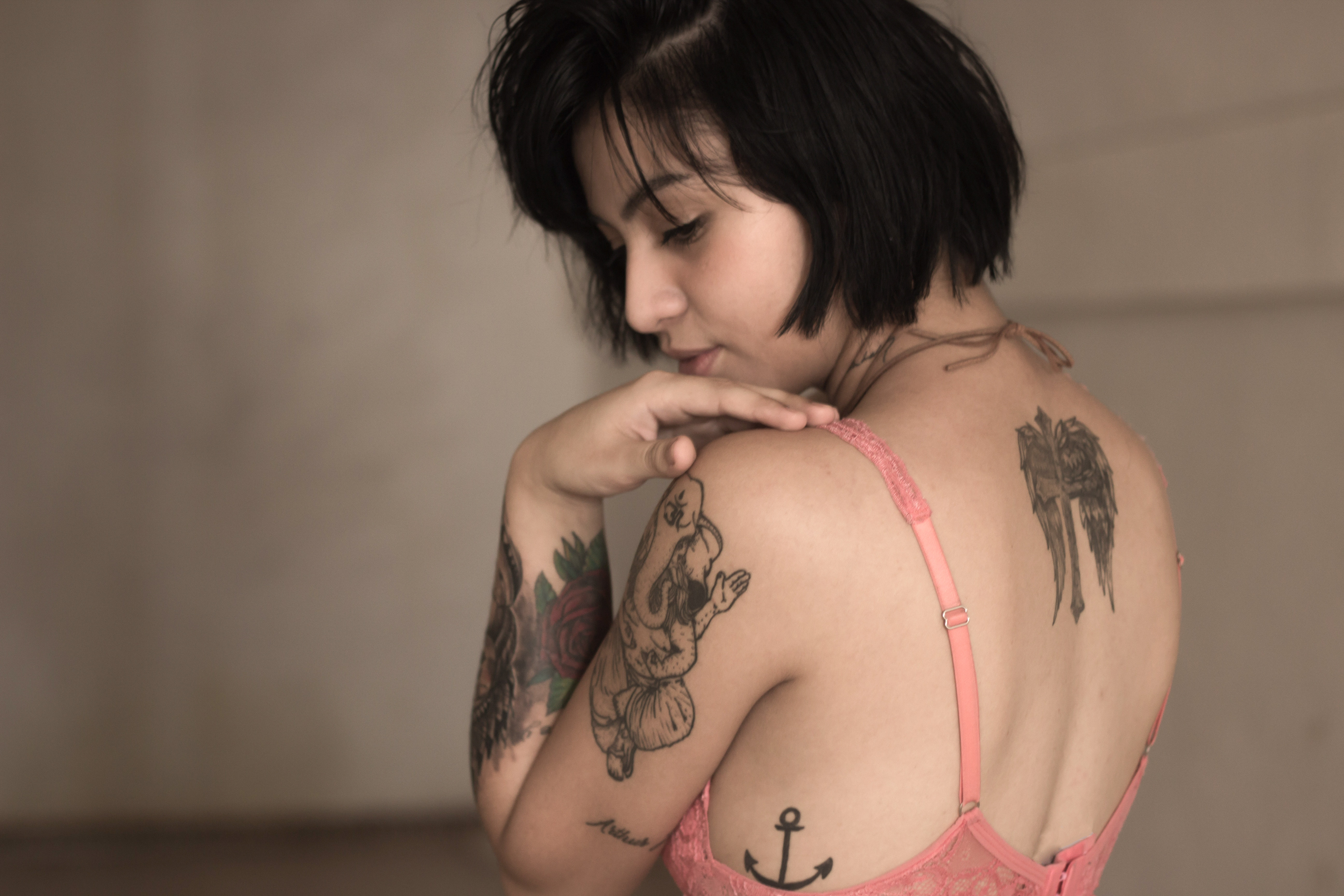 girl with tattoos on her shoulders looking back