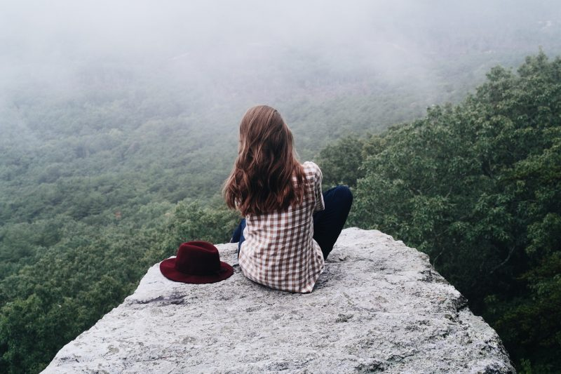 woman sitting on a mountain overlooking the fields embracing the 'i don't knows'