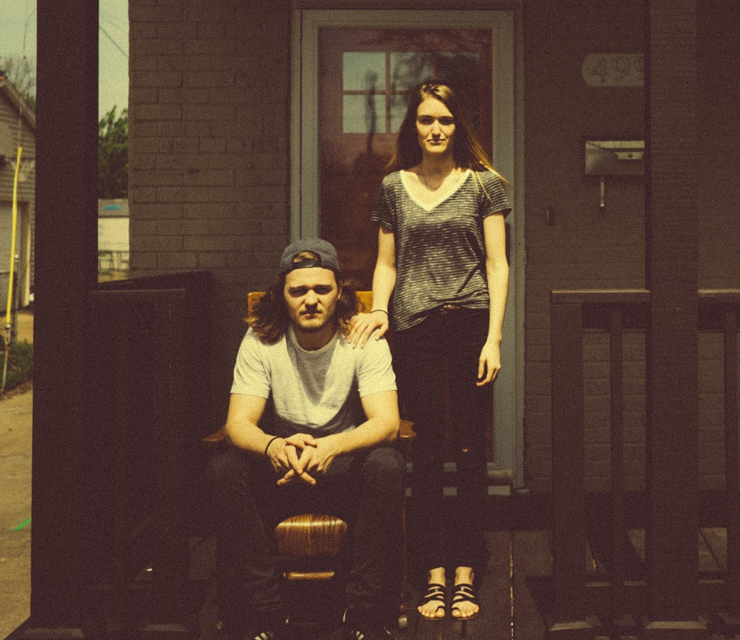 somber couple standing in front of a house