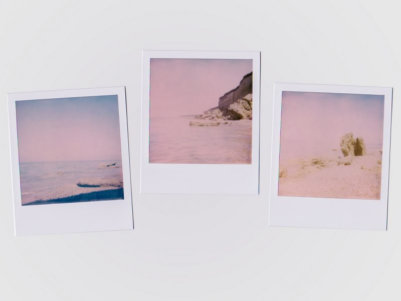 Polaroid pictures on a white desk poetry about your lips and longing