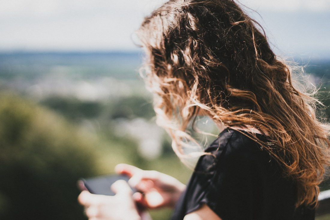 girl looking down at phone