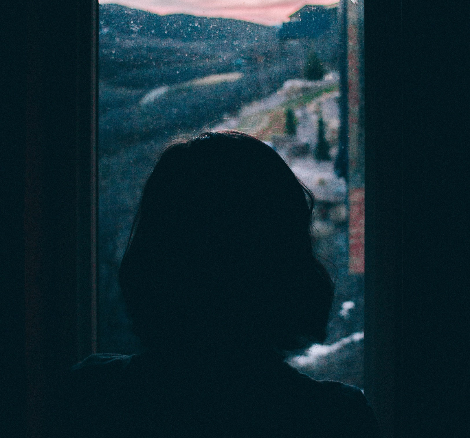 girl looking out small window