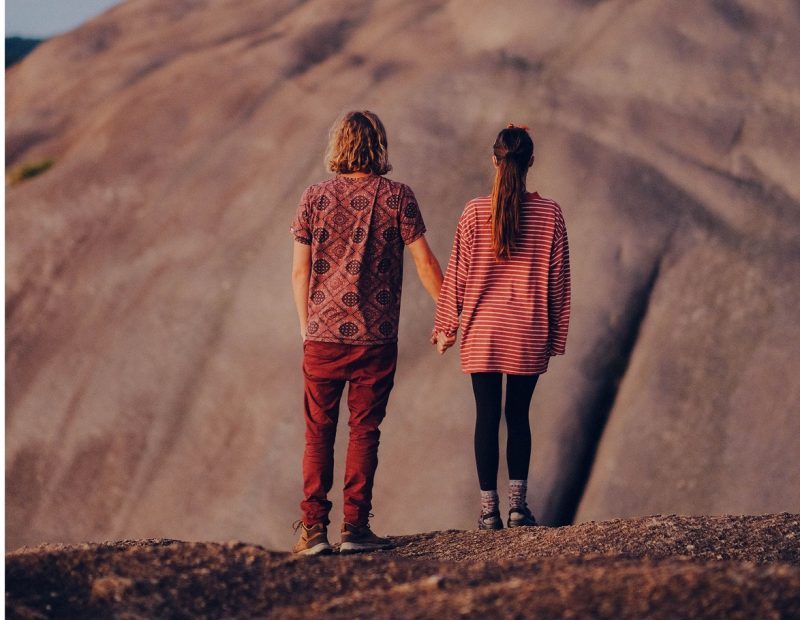 couple holding hands in front of a mountain