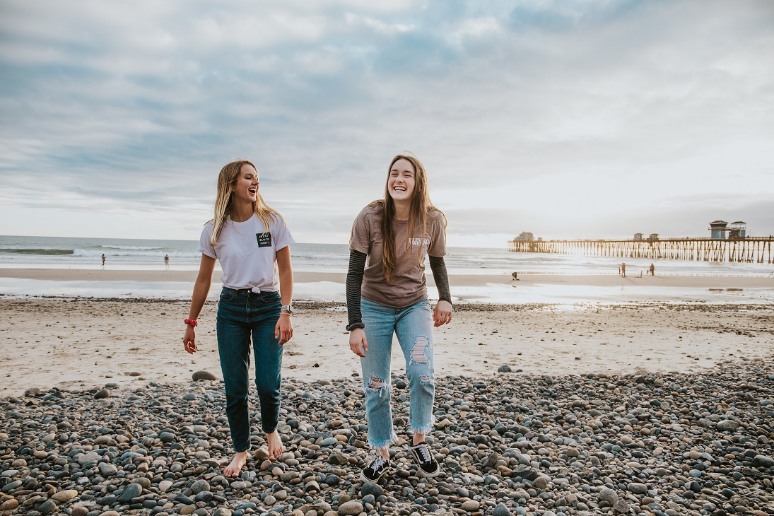 girls laughing together on the beach