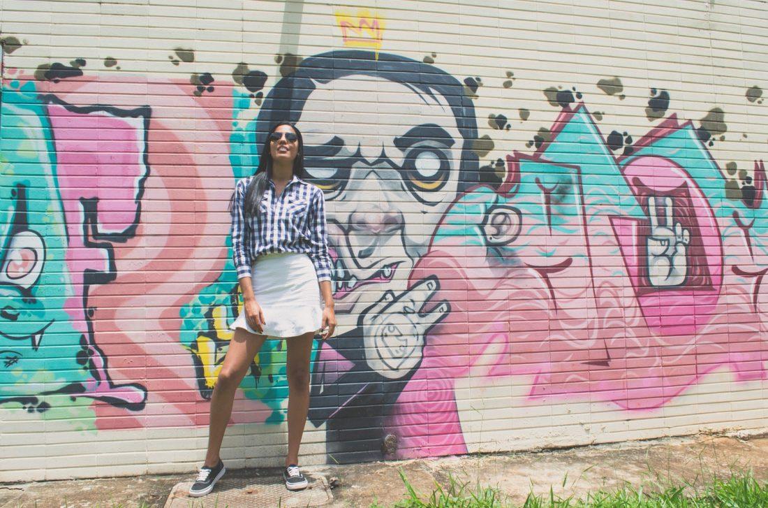 girl standing before graffiti wall