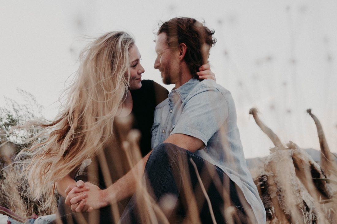 girl with hand around man's neck gently smiling