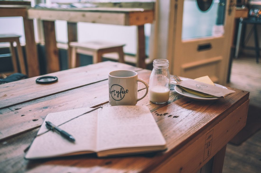 book and coffee on wooden table