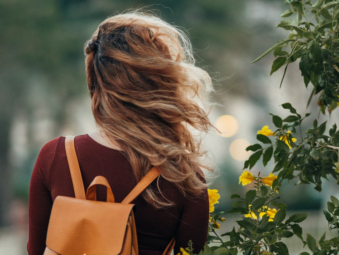 girl with orange backback and hair blowing in the wind