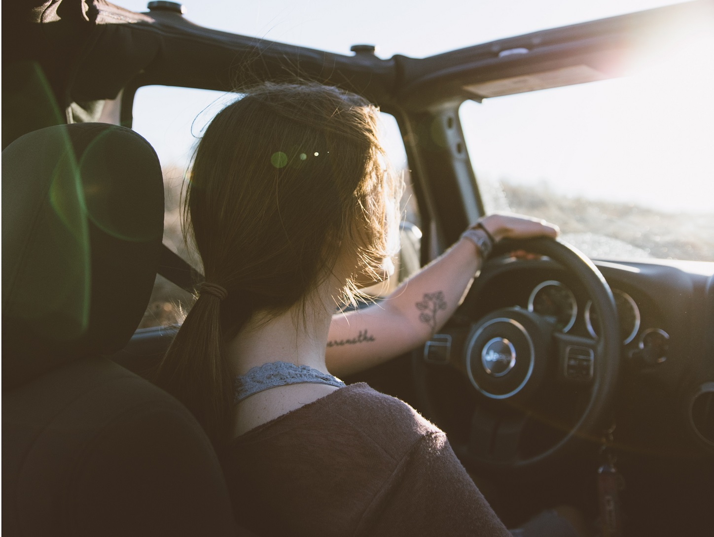 girl driving a car at sunset who can't help but wonder