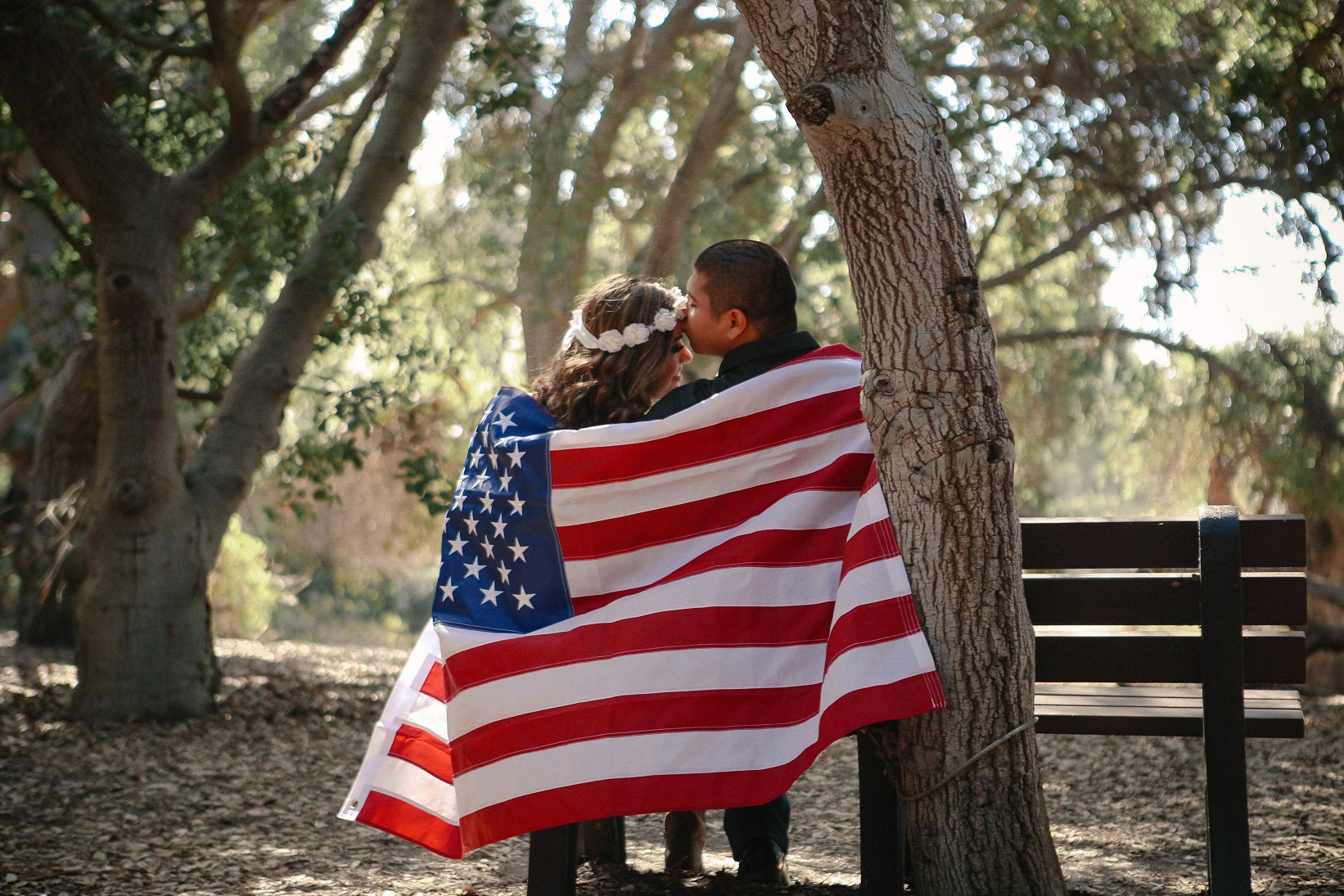 couple kissing under an American flag