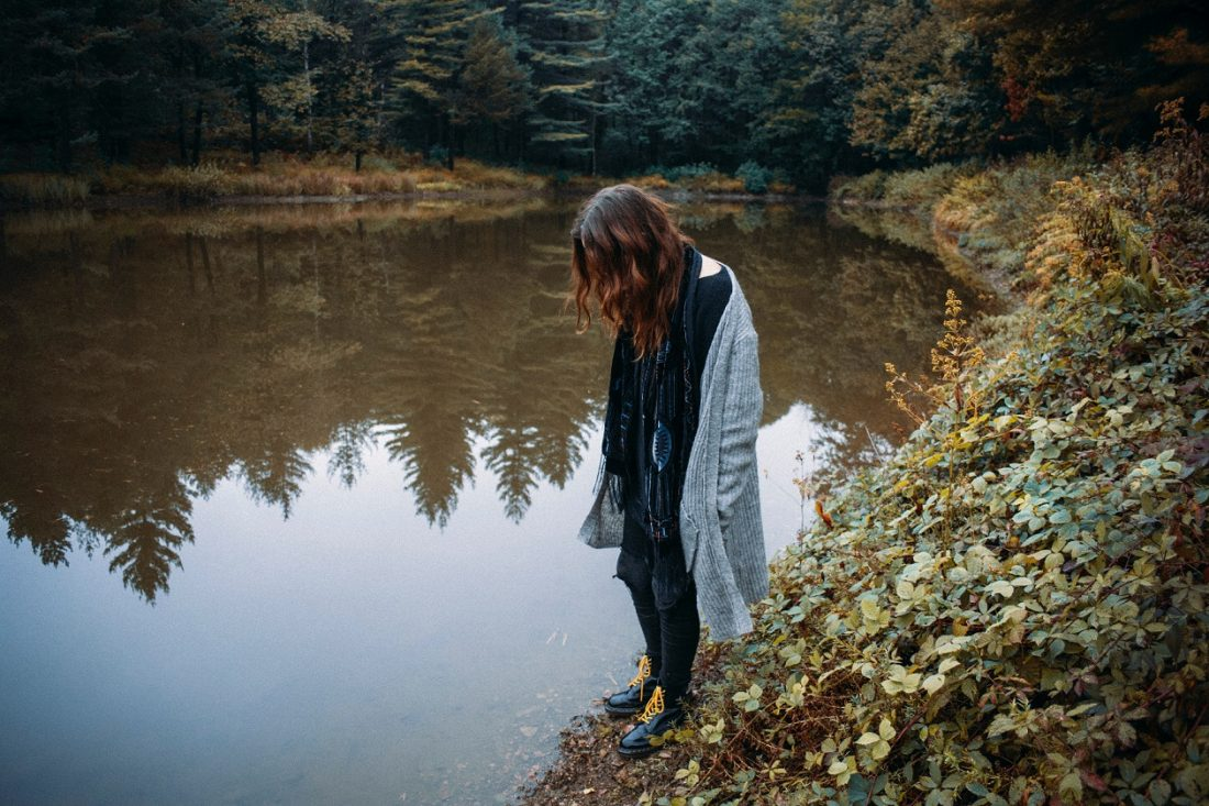 girl standing by a pond looking down