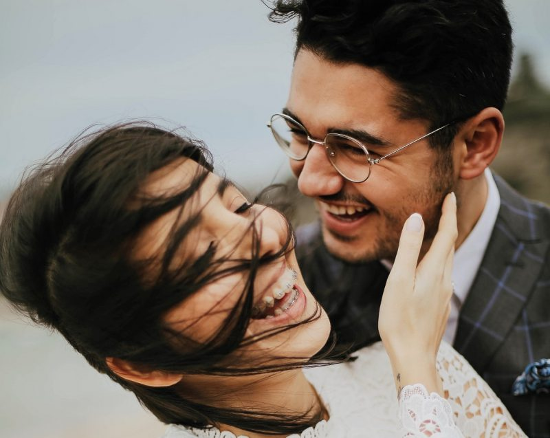 young couple laughing and smiling, love is an action