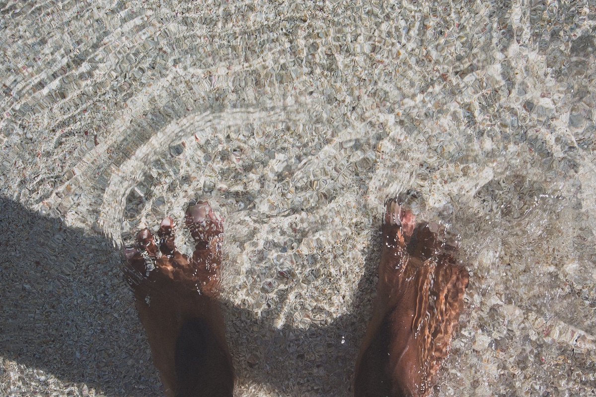 girl with feet in the ocean water, embracing who I am