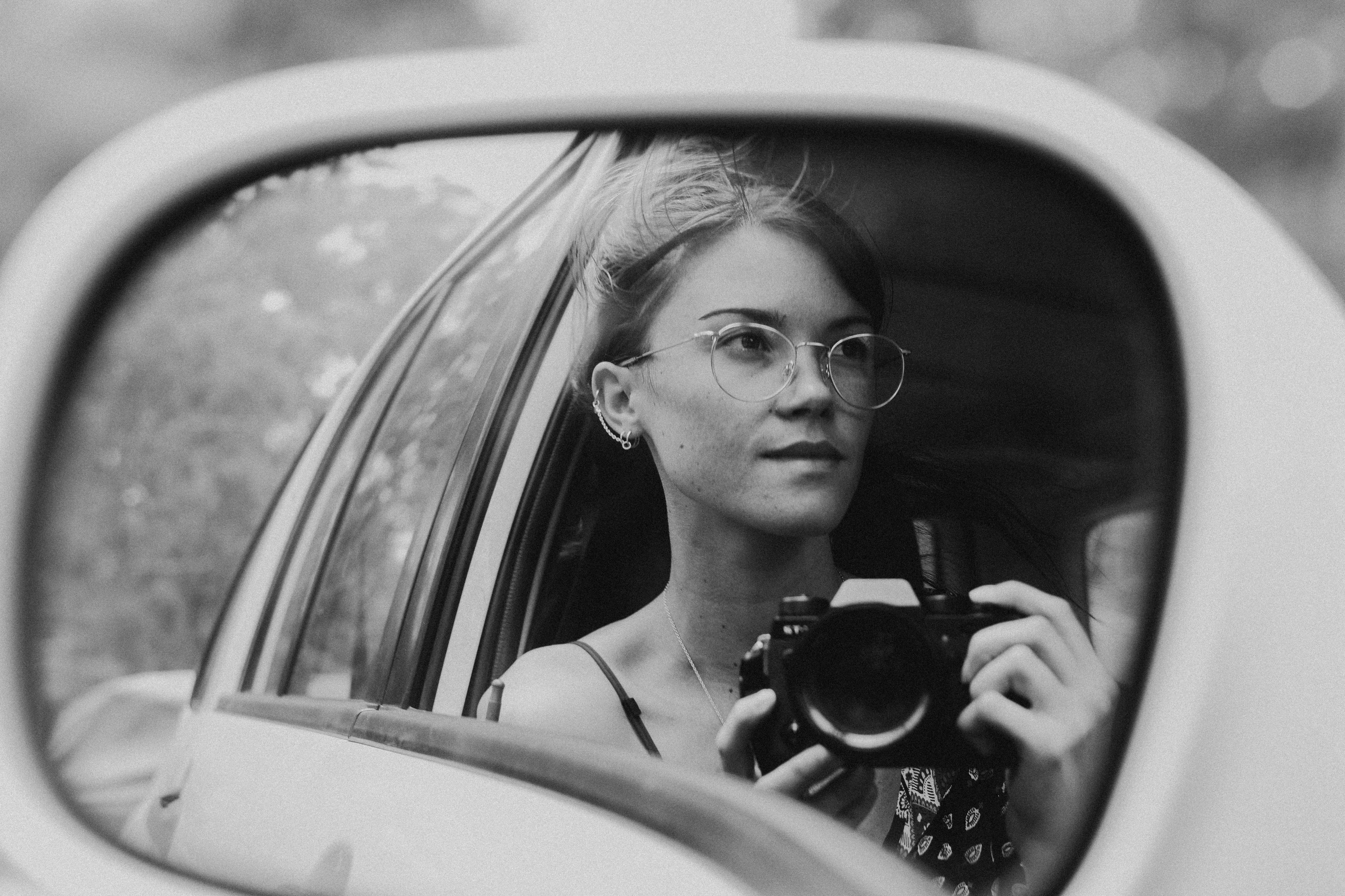 girl taking a picture in a car mirror overcoming fear