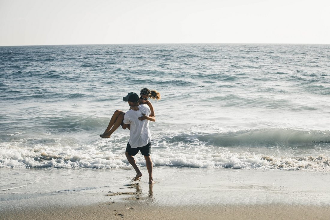 guy holding girl and playfully throwing her in ocean