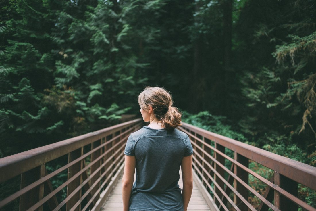 girl looking away while standing on a bridge