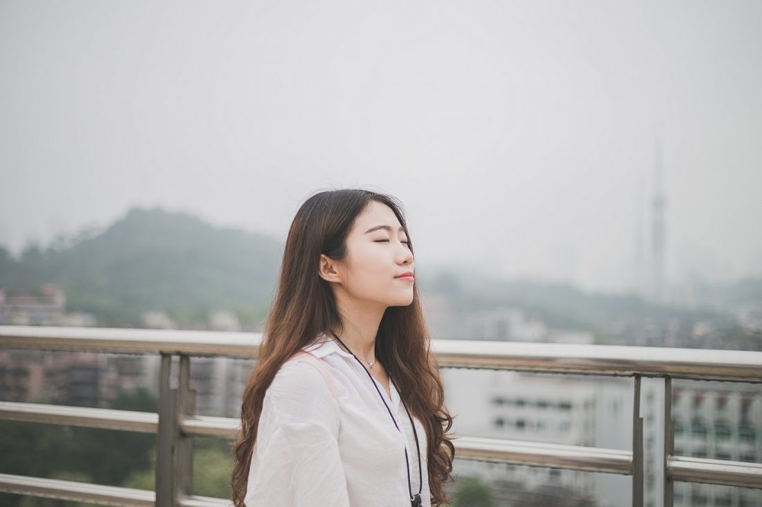 girl with eyes closed on cloudy day