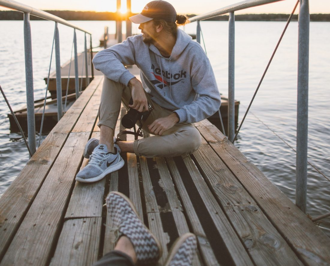 couple sitting separated on a fishing dock