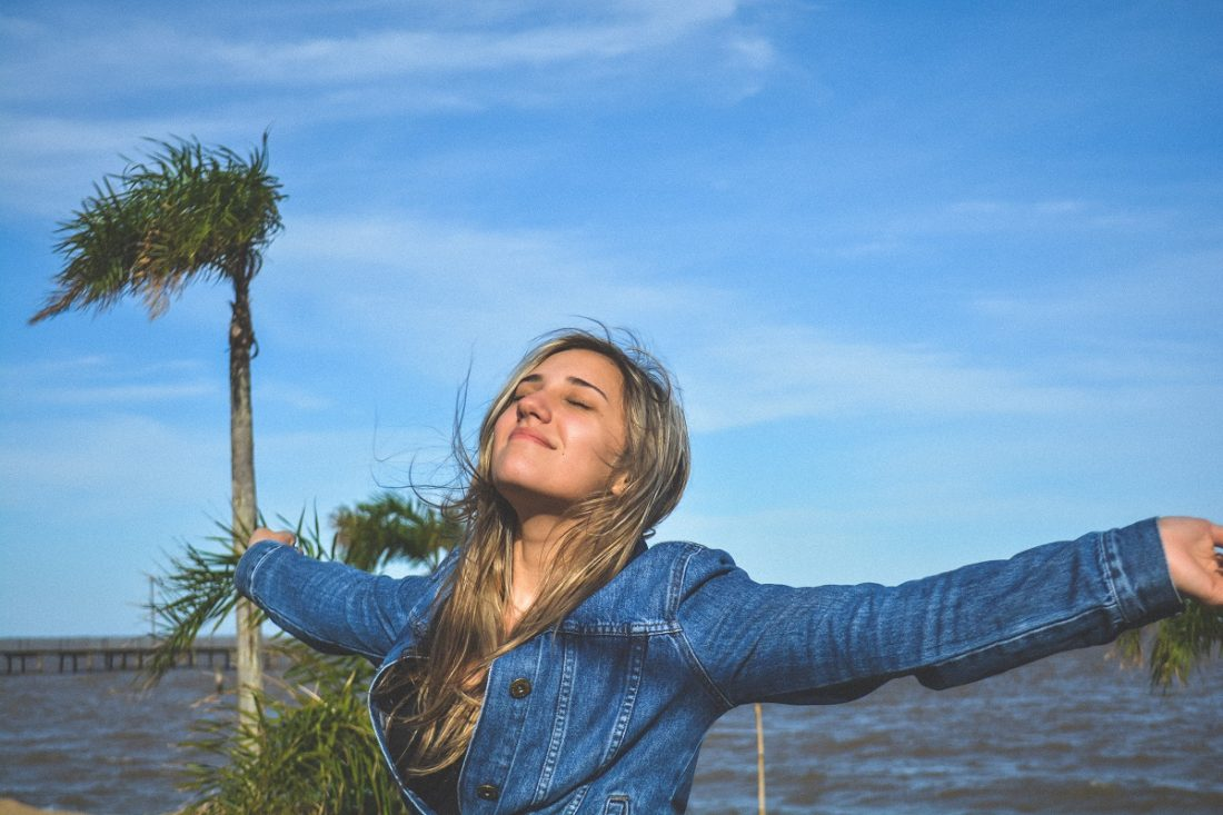 girl with arms outstretched looking up at the sky, feeling life, what life feels like