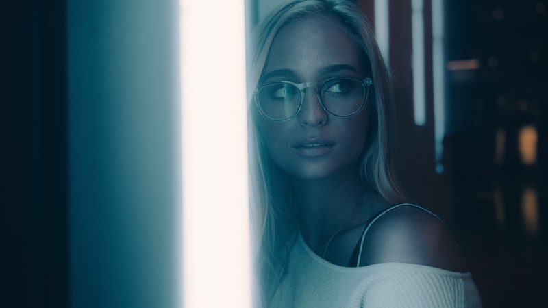 girl with glasses standing in front of a bright light