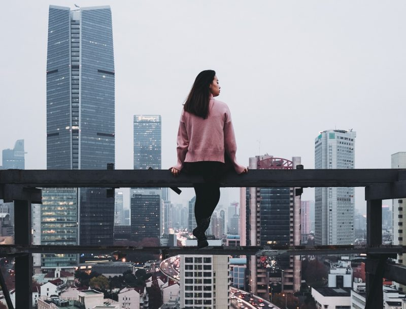 girl sitting on balcony learning to surrender to the universe