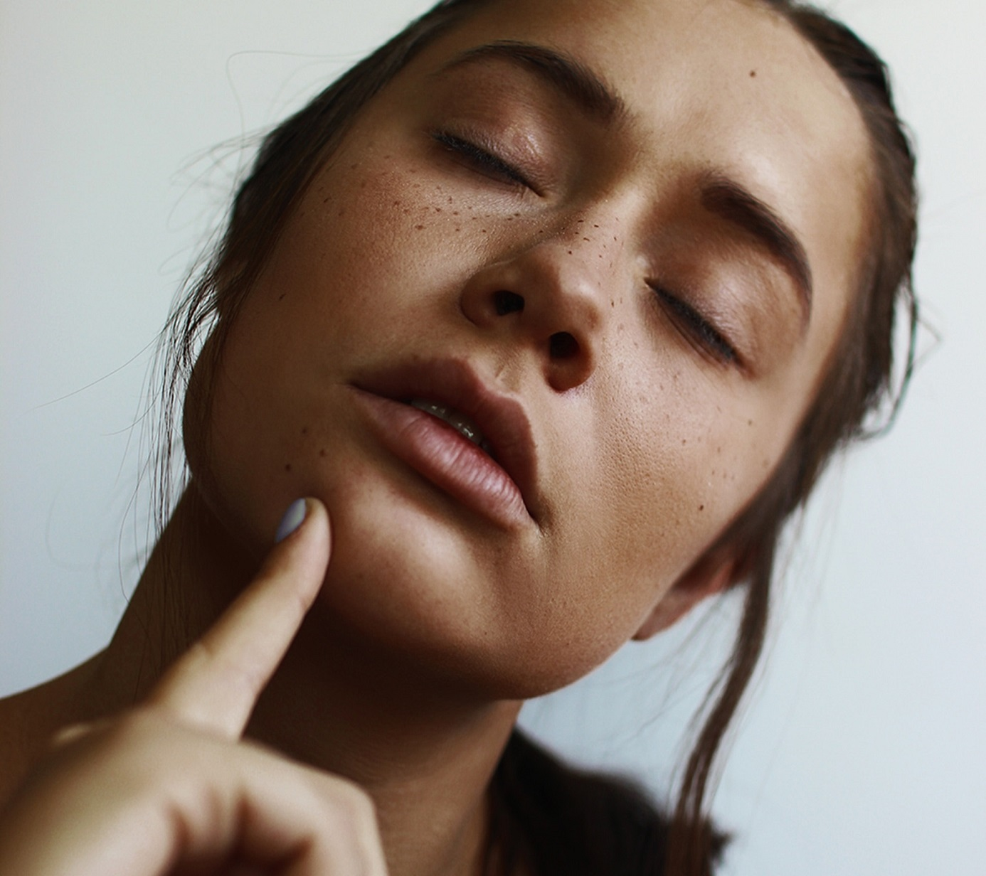 girl with freckles pointing at her chin