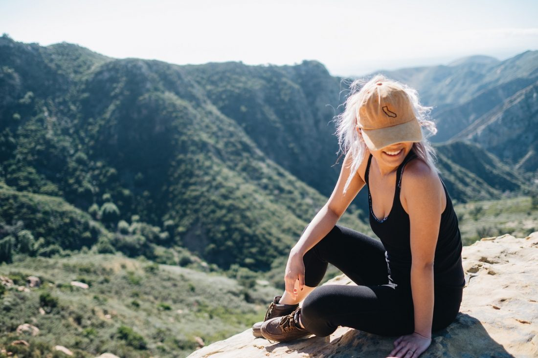 girl with california hat sitting on a mountain
