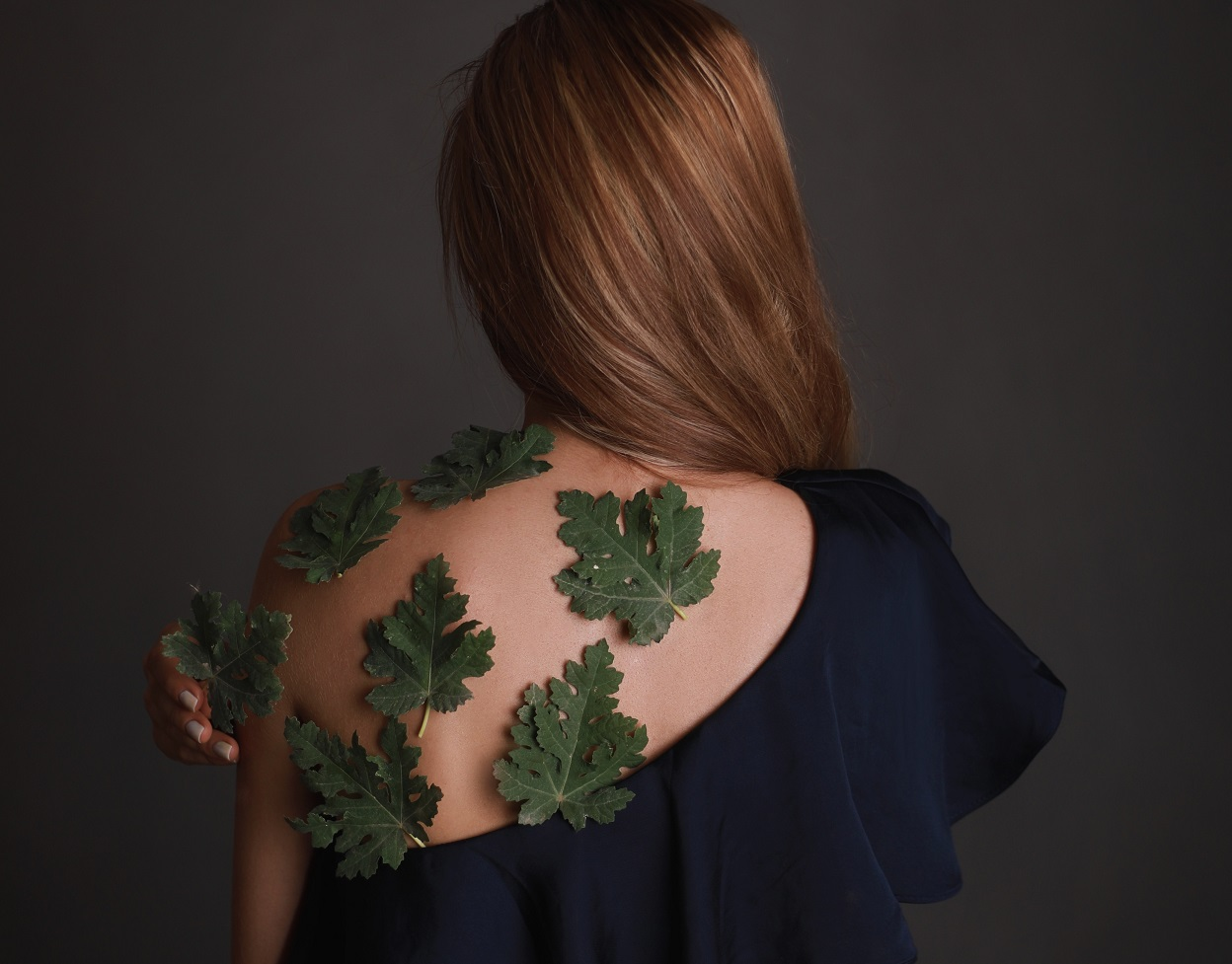 girl with leaves on her back facing away from the camera