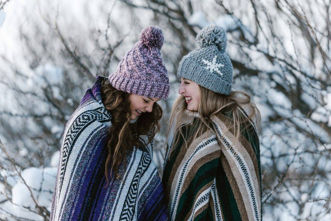 happy girls laughing in winter snowstorm