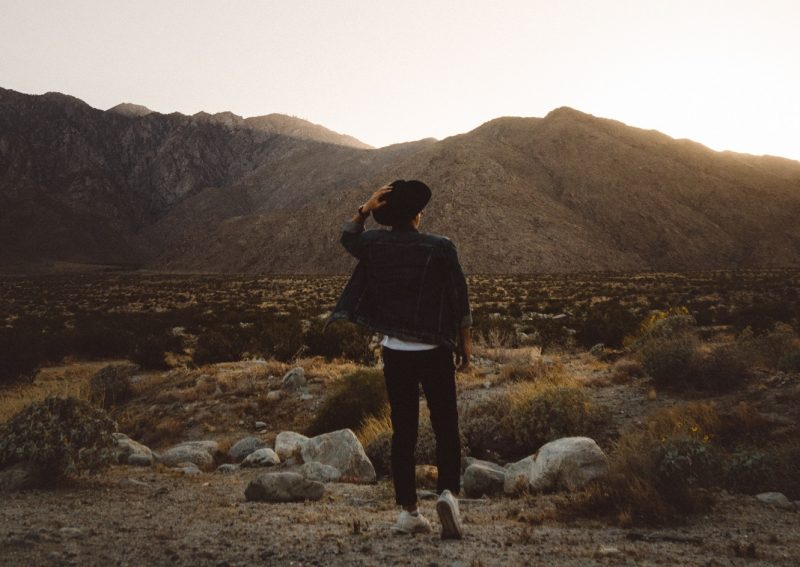 person with hat overlooking mountains, god is bigger than we think