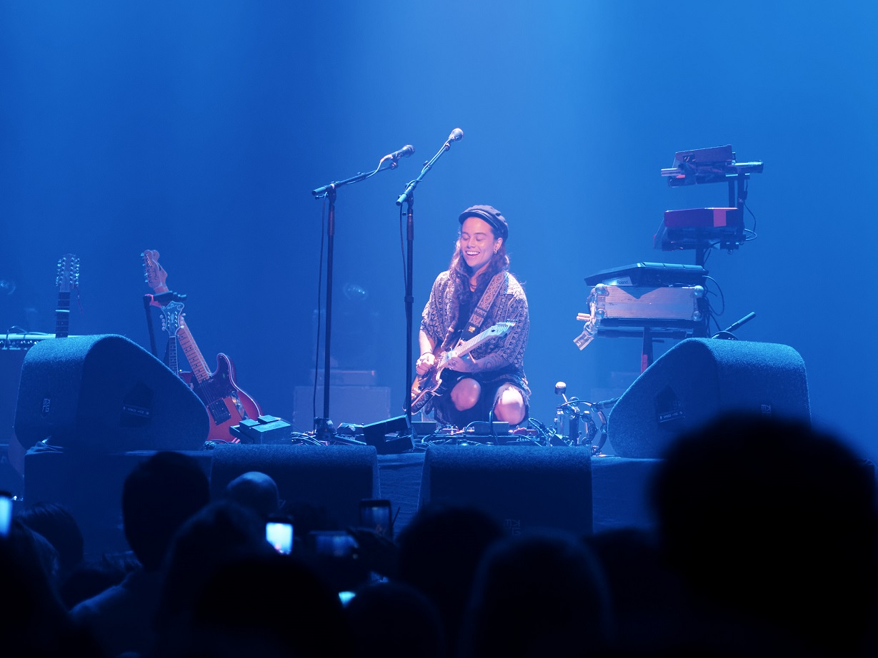 Tash Sultana smiling and playing on stage during show