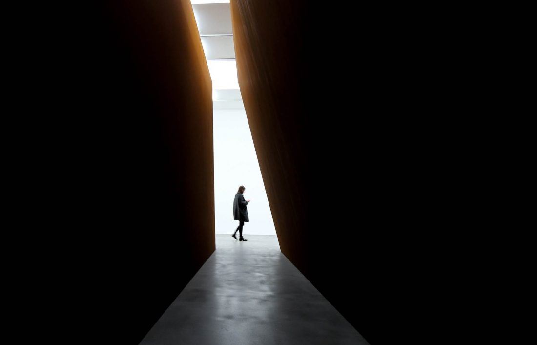 person walking through shaded tunnel