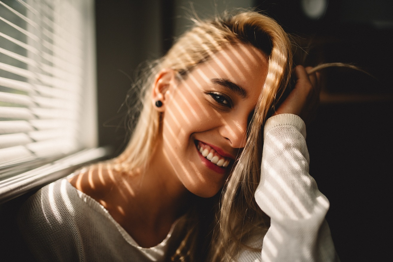 woman smiling with light from windows across her face