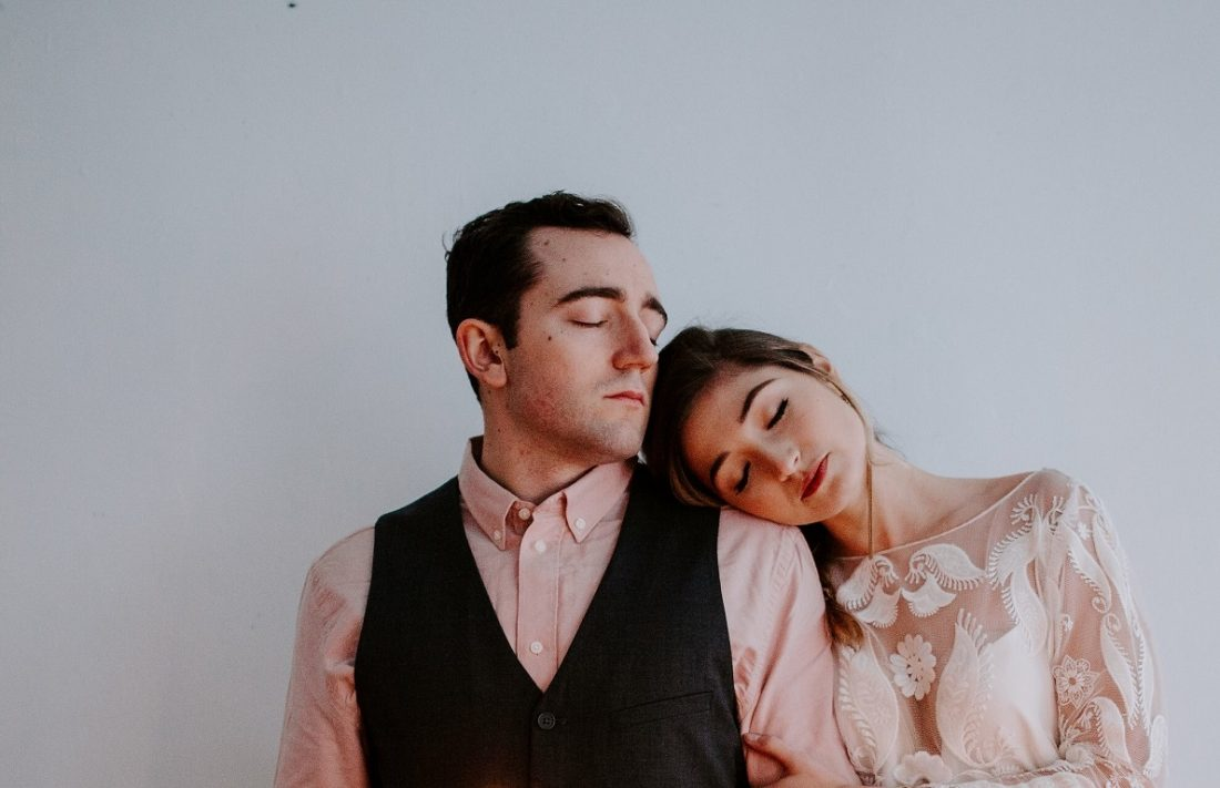 couple with close eyes leaning on each other's shoulders