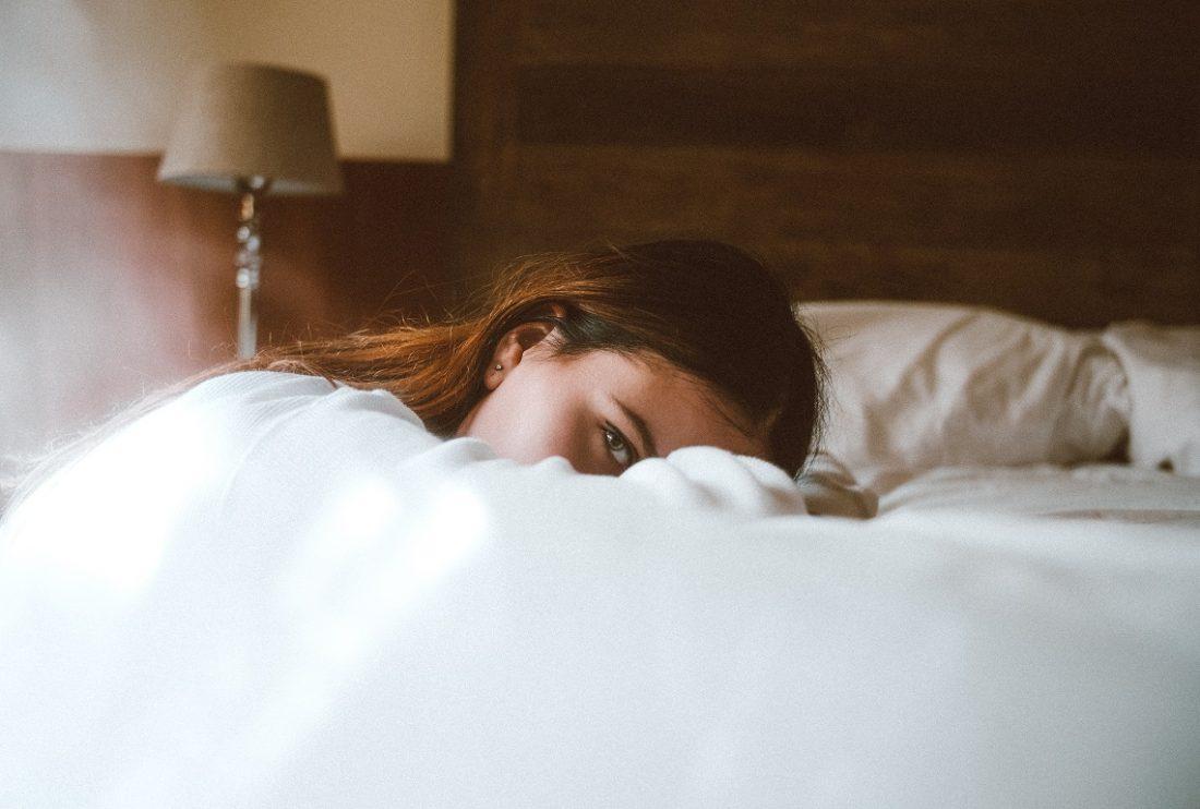 girl buried under blankets