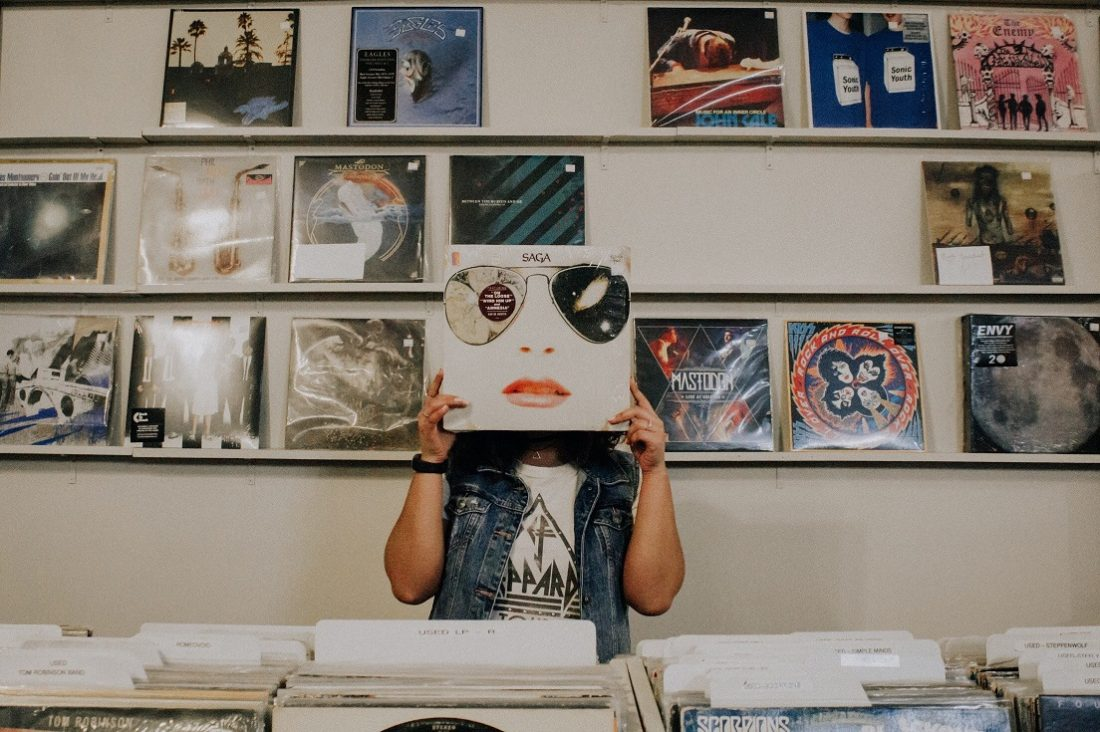 girl with record over her face at record store