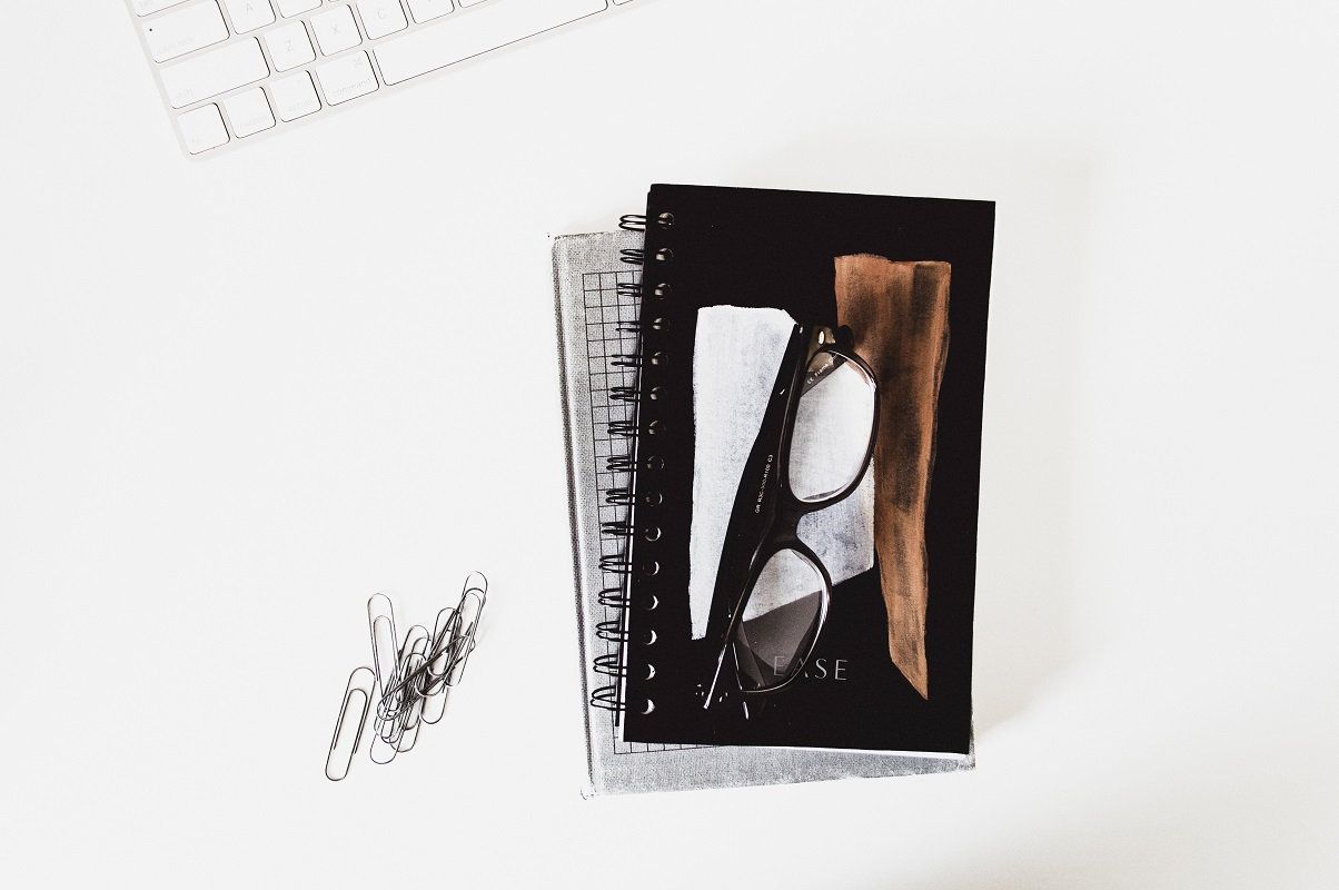 notebooks and glasses on white table