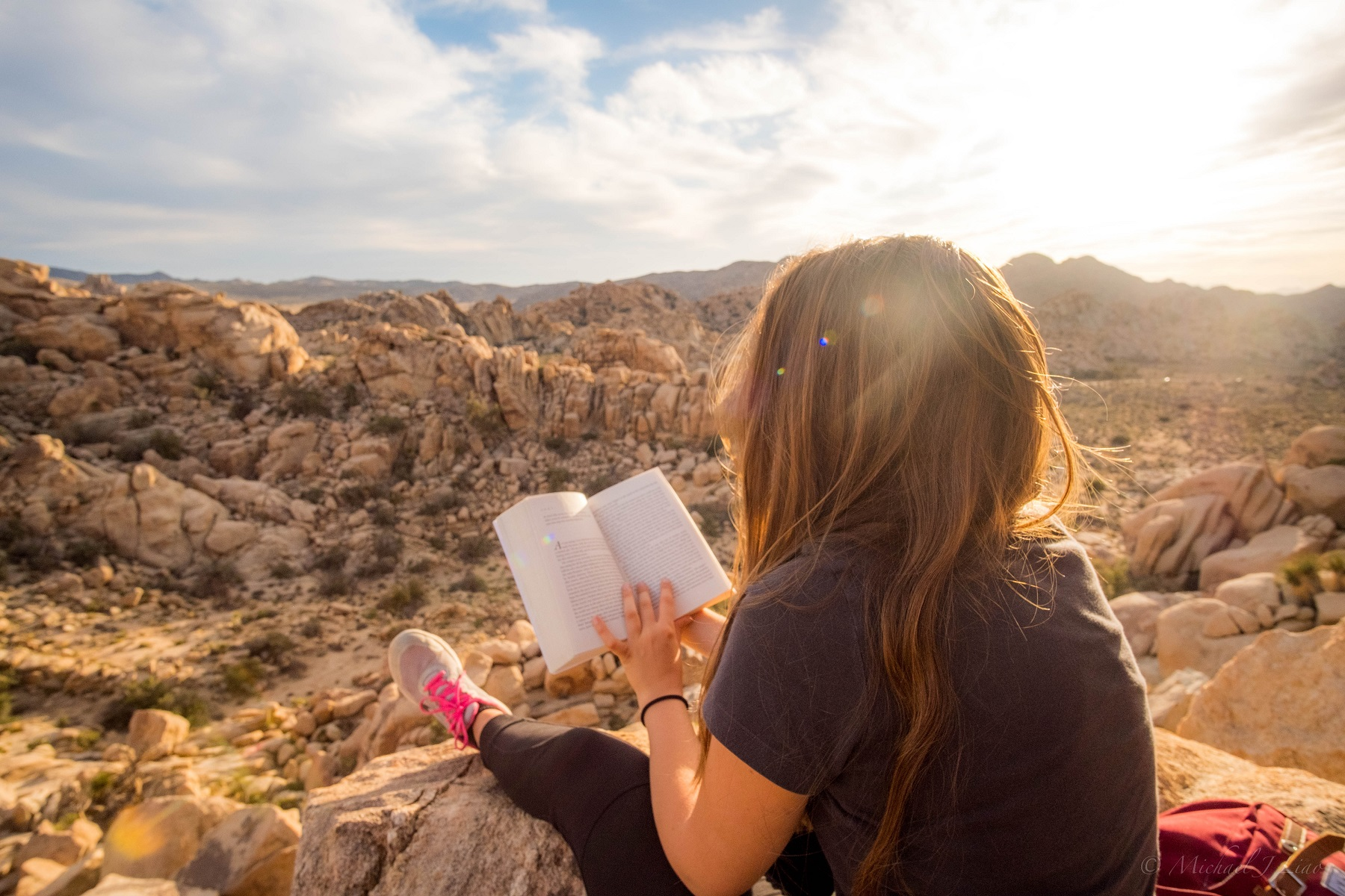 girl with book on mountain top
