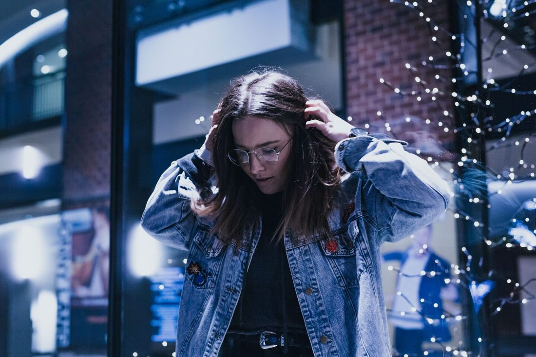 girl with hands on her head surrounded by lights