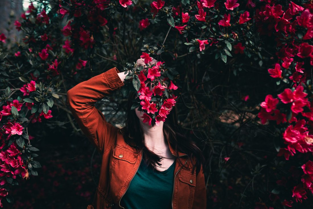 girl with pink flowers over her face, choose to rise above negativity