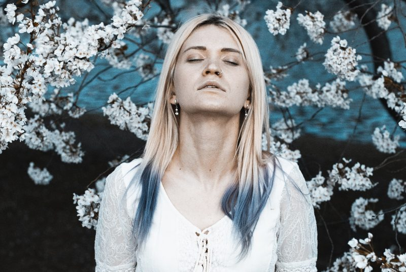 girl with blue hair standing in front of blue and white flowers, fighting feelings of inadequacy