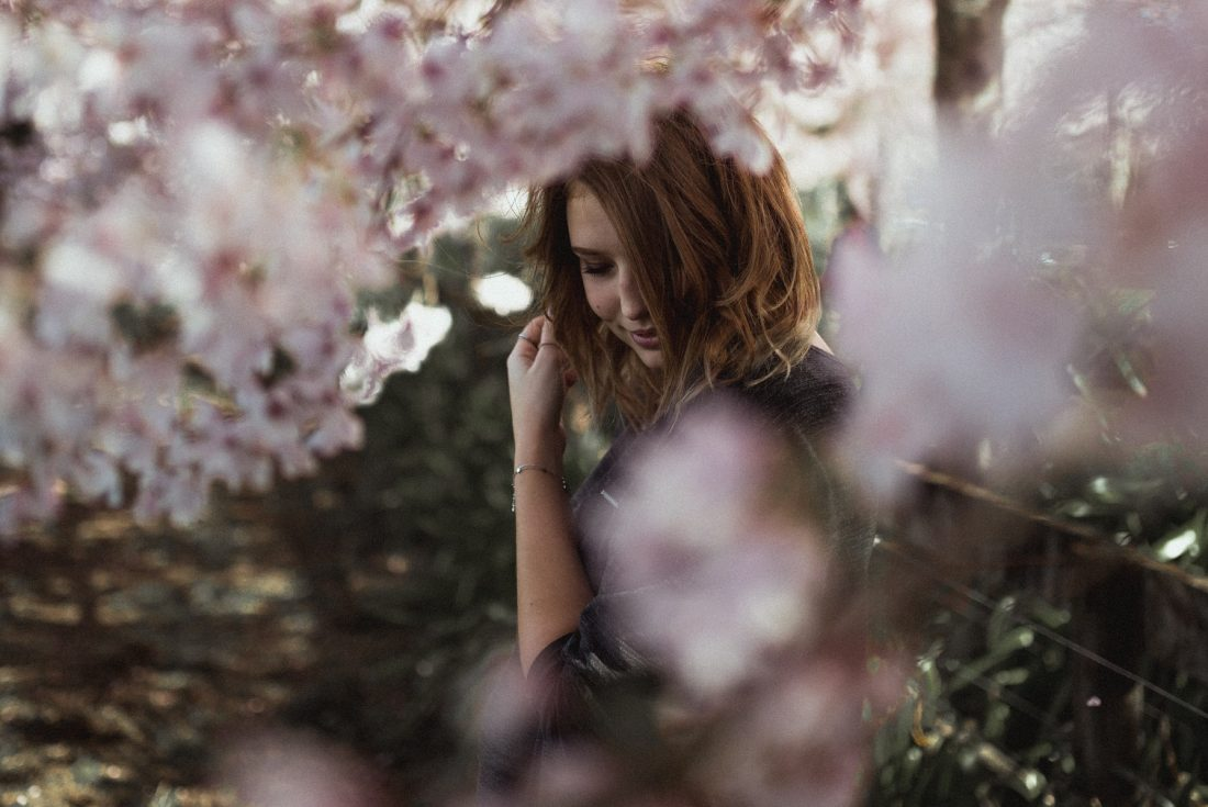 girl half-hidden by flowers, learn to live in god's holiness
