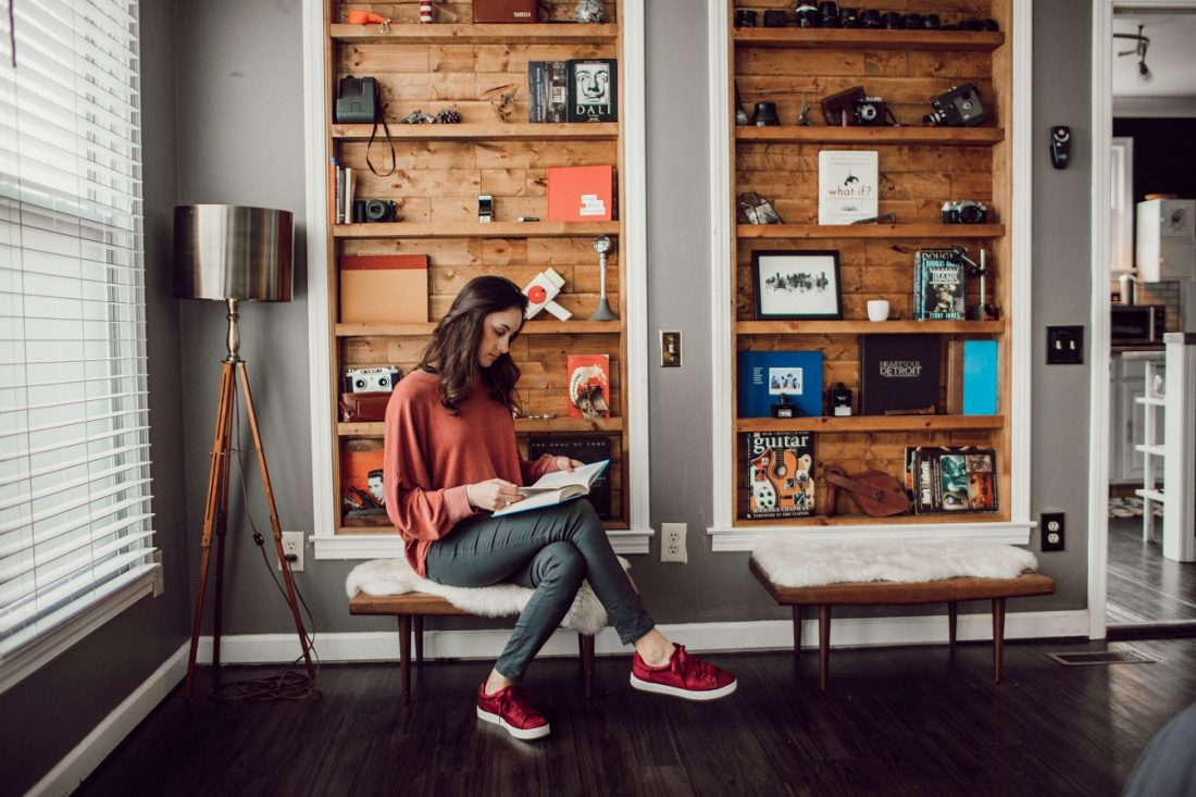 girl with book in front of shelves, what I'm reading this week