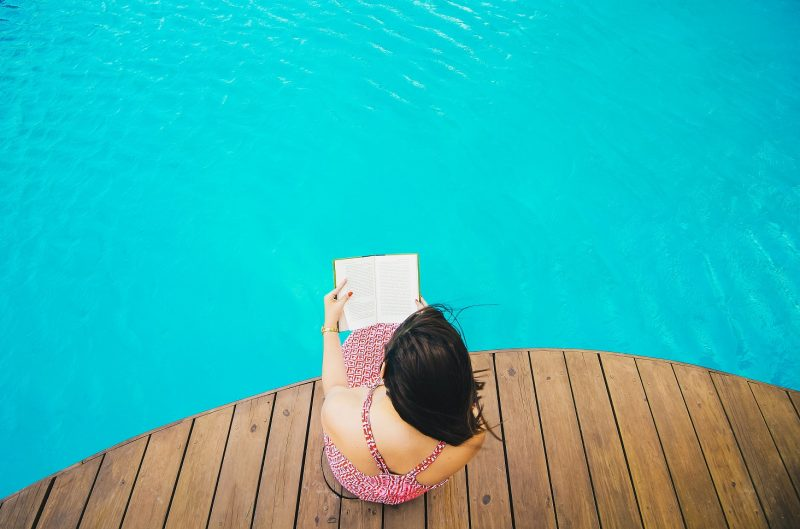girl reading book by pool, reading list june week 2